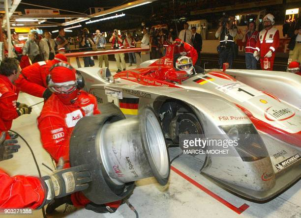 Les mécaniciens de l'équipe Audi effectuent un changement de pneumatiques sur l'Audi n·1 dans la nuit du 15 au 16 juin 2002 au circuit Bugatti du...