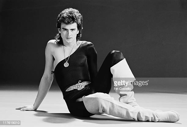 Les McKeown British pop singer poses sitting in the ground leaning on one arm wearing a oneshoulder top with a medallion hanging from a chain around...
