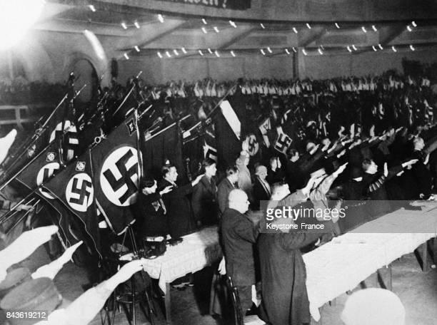 Les membres du parti nationalsocialiste effectuent le salut nazi lors d'un grand rassemblement au Palais des Sports le 7 janvier 1933 à Berlin...
