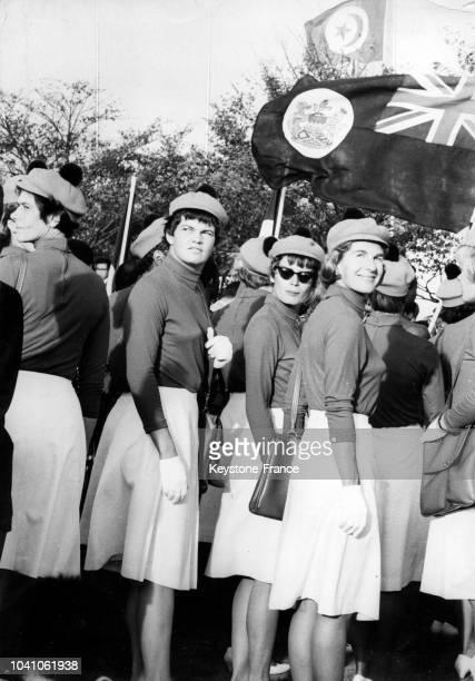 Les membres féminins de l'équipe olympique canadienne assistent à la levée de leur drapeau au Village olympique en octobre 1964 à Tokyo Japon