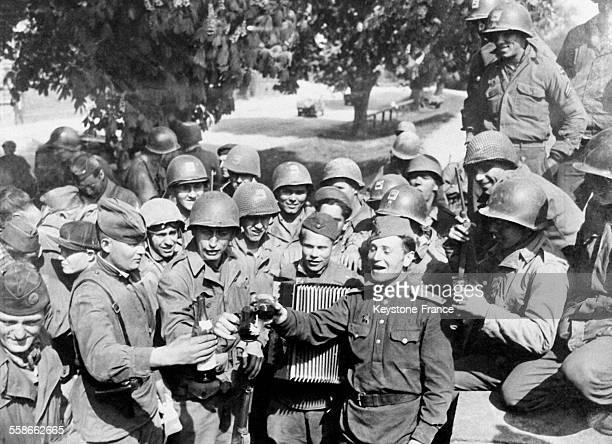 Les militaires boivent un verre de vin pour fêter la jonction des deux armées sur un air d'accordéon à Torgau Allemagne en mai 1945
