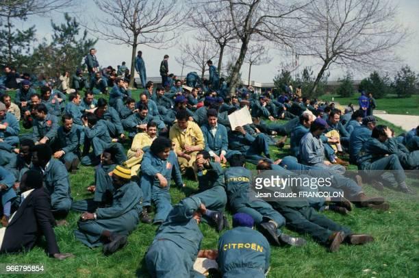 Les ouvriers grévistes de l'usine Citroen assis sur les pelouses en signe de protestation le 18 avril 1984 à Aulnay-sous-Bois, France.