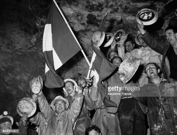 Les ouvriers heureux brandissent un drapeaux italien et suisse après avoir fait tombé le dernier mur séparant l'Italie de la Suisse le 5 avril 1962