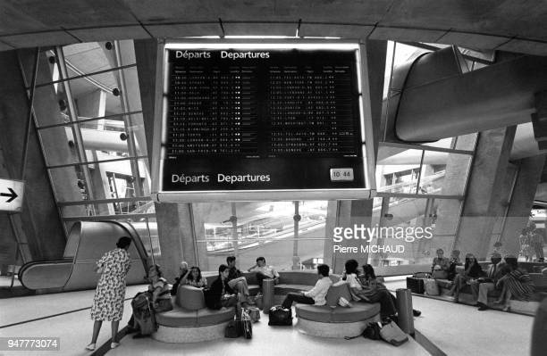 Les passagers dans une salle d'attente avec le tableau des départs à l'aéroport de Roissy, en France.