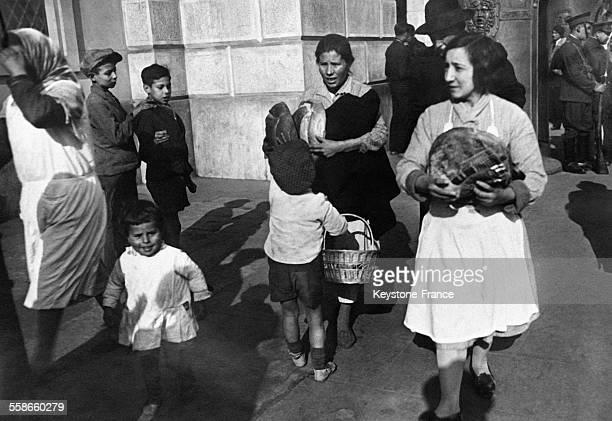 Les pauvres quittant la Capitainerie Générale portant le pain béni par l'Evêque de Barcelone Espagne le 29 janvier 1931