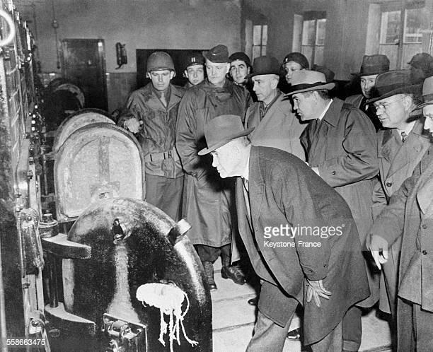 Les politiques et soldats américains devant les portes ouvertes des fours crématoires au camp de concentration et d'extermination de Buchenwald à...