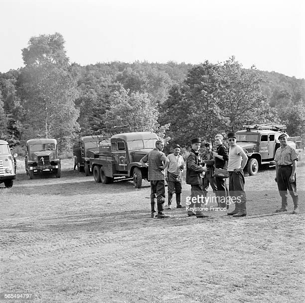 Les pompiers et combattants du feu boivent un verre devant leurs camions dans une clairière de la forêt de Fontainebleau France circa 1960