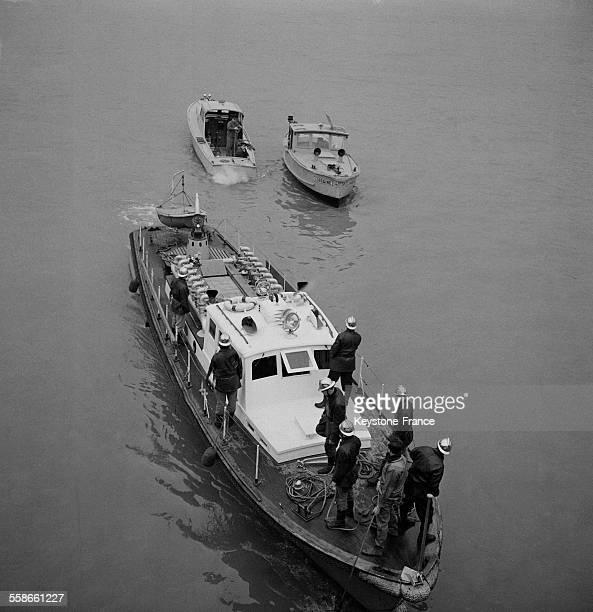 Les pompiers recherchant l'épave dans la Seine à IvrysurSeine France le 15 janvier 1961
