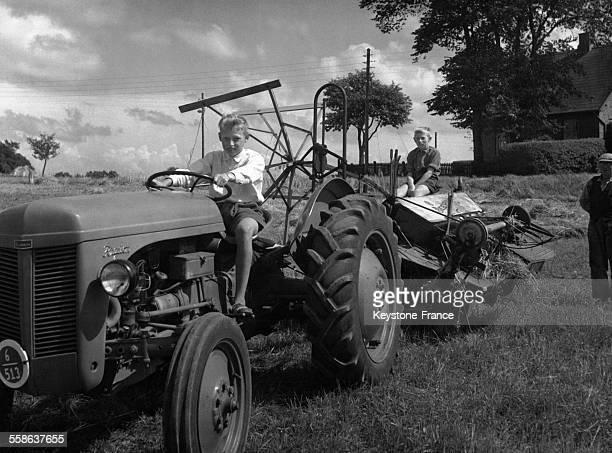 Les princes Ingolf et Christian fils du prince Knud frère du roi Frédéric IX en vacances à la campagne jouent au fermier et conduisent un tracteur au...
