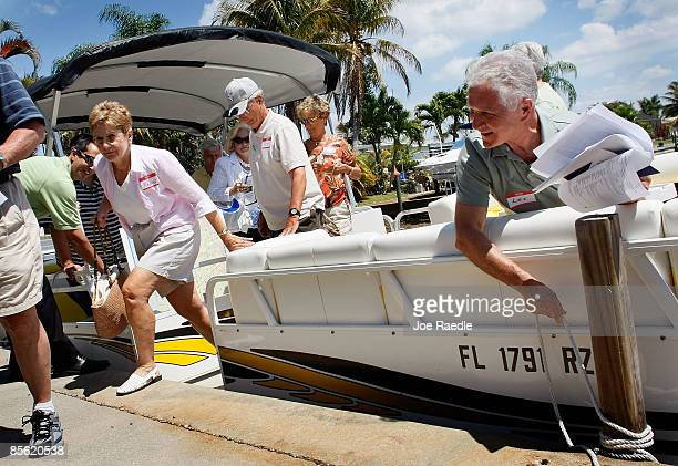 Les Renkey holds the rope to a mooring as others looking to buy a home at a good price get off the boat as they take part in a foreclosure boat tour...