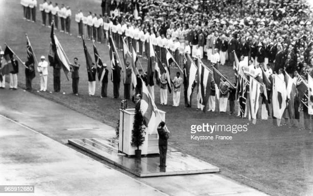 Les représentants des équipes des différentes nations dont les drapeaux sont présents tout autour du stade prêtent serment à la tribune lors des Jeux...