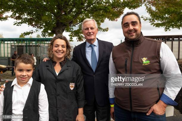 Les Republicains Presidential candidate Michel Barnier poses with a family breeding Aubrac cows during the inauguration of the 10,000 square metre...