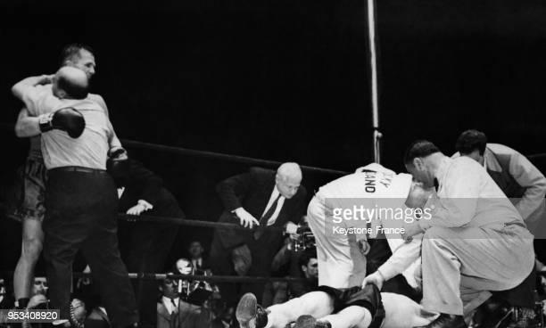 Les soigneurs raniment le boxeur Rocky Graziano vaincu par KO, pendant que l'arbitre tire sur son short et que le vainqueur Tony Zale est félicité au...