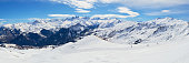 Les Sybelles ski domain in France. Panorama with slopes, skiers, and mountain peaks, on a sunny day with blue sky.