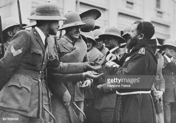 Les volontaires italiens s'embarquant pour la Somalie discutent avec un prêtre en Italie en mars 1935