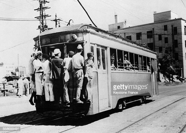 Les voyageurs qui n'ont pas pu trouver de places à bord du tramway s'accrochent à l'extérieur dans une position périlleuse à Tokyo Japon le 3 octobre...