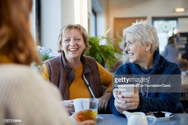lesbian couple and adult daughter drinking coffee and talking in cafe - lgbtq stock pictures, royalty-free photos & images