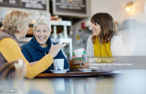 lesbian couple and adult daughter drinking coffee and talking in cafe - mature women stock pictures, royalty-free photos & images