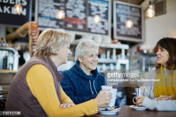 lesbian couple and adult daughter drinking coffee and talking in cafe - cef do not delete stock pictures, royalty-free photos & images