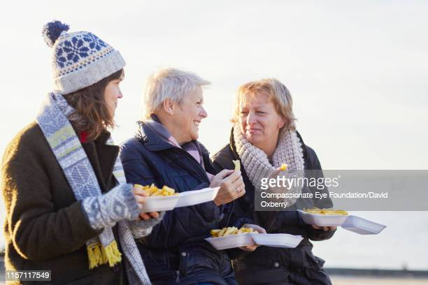 lesbian couple and adult daughter eating fries by sea - cef do not delete stock pictures, royalty-free photos & images