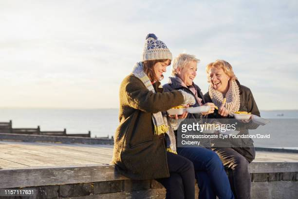 lesbian couple and adult daughter eating fries by sea - three people stock pictures, royalty-free photos & images
