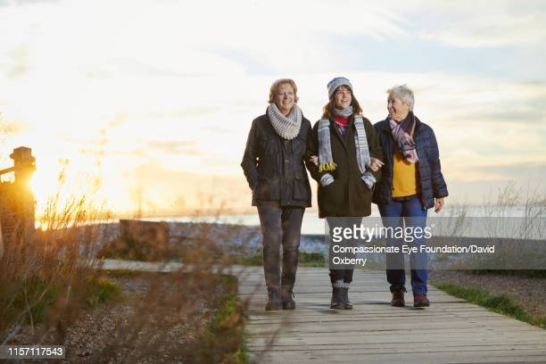 lesbian couple and adult daughter on walkway by sea at sunset - mature adult stock pictures, royalty-free photos & images