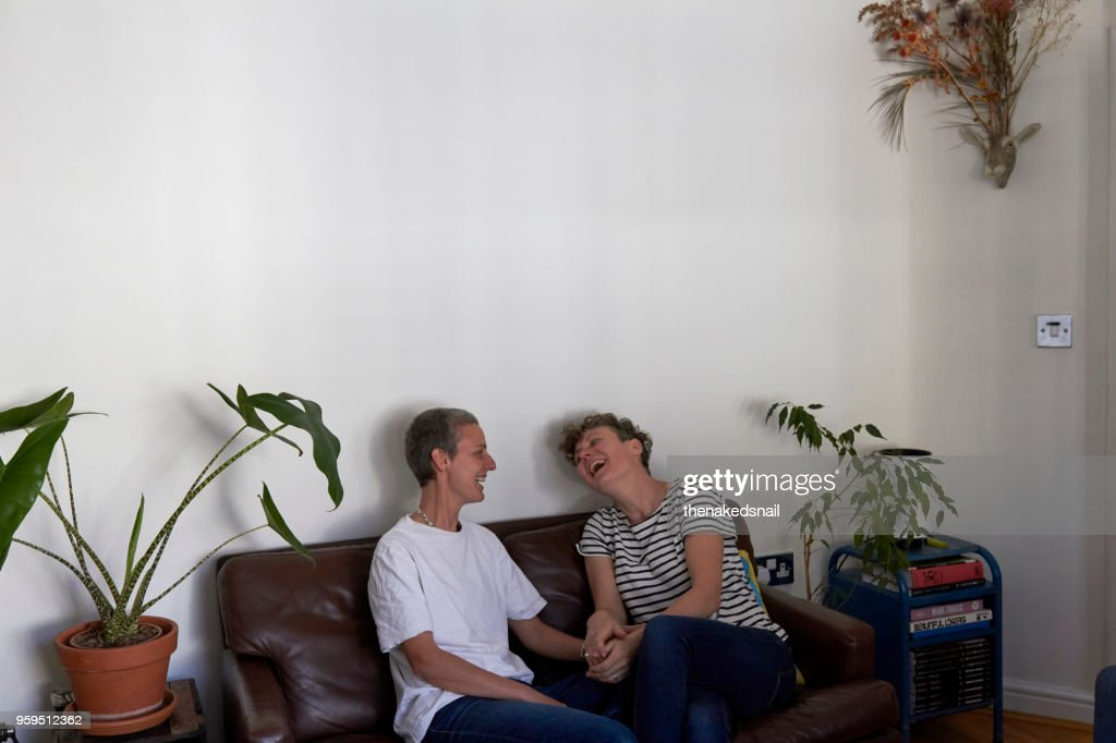 Lesbian couple at home, laughing on the sofa : Stock-Foto