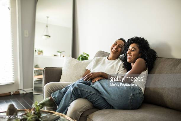 Lesbian couple at home snuggling on couch