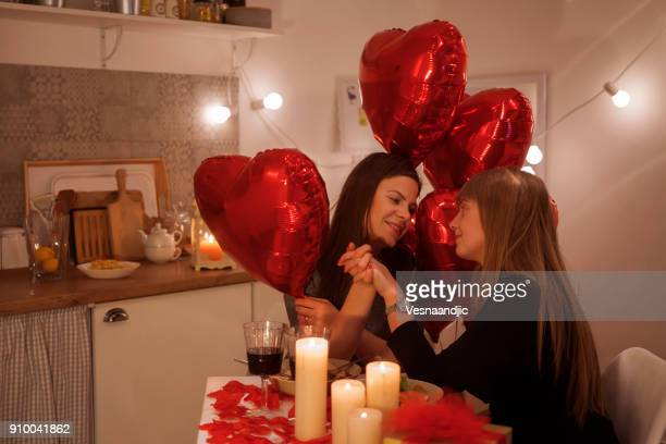 lesbian couple celebrating valentine's day - valentines day dinner stock pictures, royalty-free photos & images