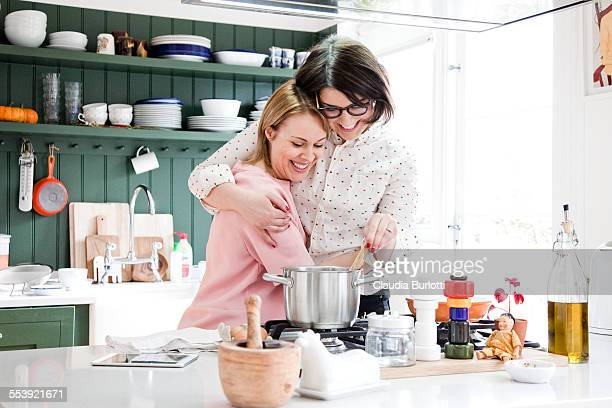 Lesbian couple cooking at home