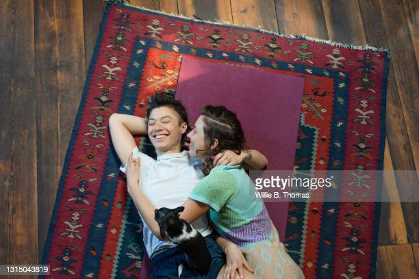 lesbian couple cuddling and laughing on the floor - lying down stock pictures, royalty-free photos & images