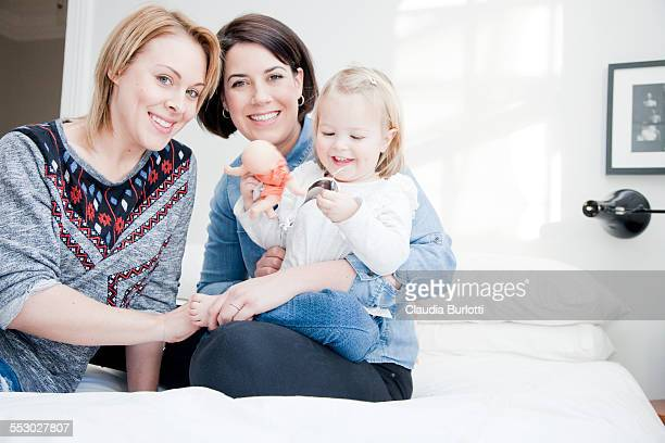lesbian couple cuddling their daughter in bed - family with one child stock pictures, royalty-free photos & images