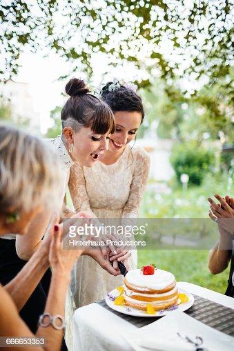 Lesbian couple cutting their wedding cake
