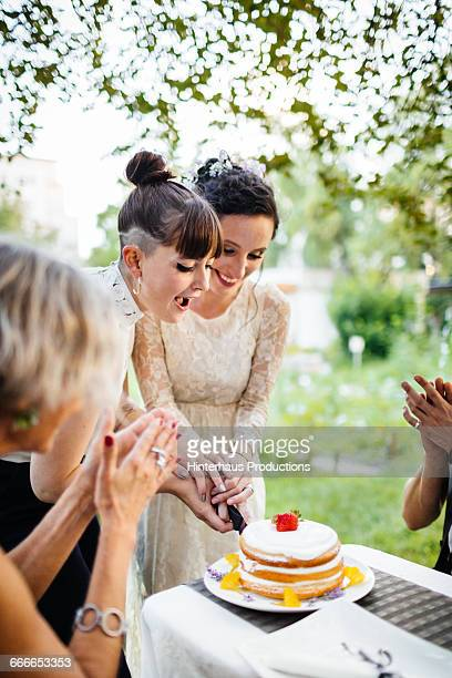 Lesbian couple cutting their wedding cake