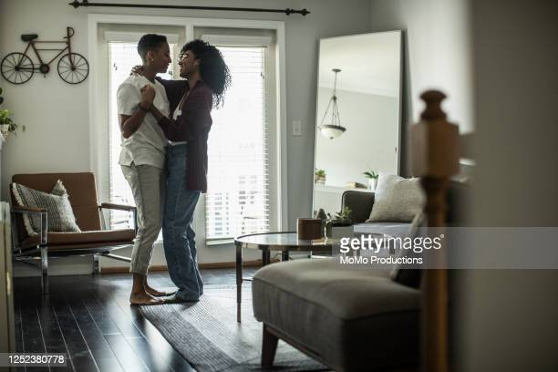 lesbian couple dancing in living room - black hair stock pictures, royalty-free photos & images