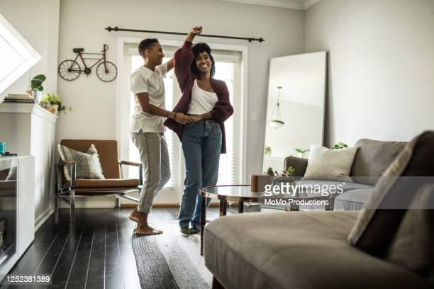 lesbian couple dancing in living room - nosotroscollection stock pictures, royalty-free photos & images