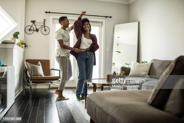 lesbian couple dancing in living room - nosotroscollection stockfoto's en -beelden