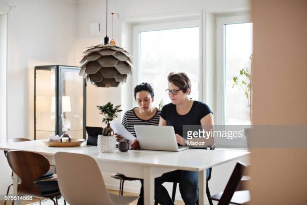 lesbian couple discussing financial bills over laptop while sitting at table - home insurance stock pictures, royalty-free photos & images
