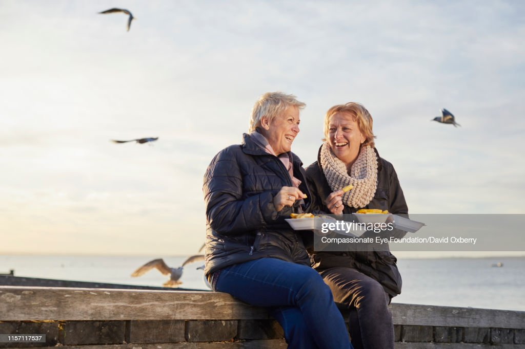 Lesbian couple eating fries by sea : Stock Photo