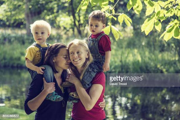 Lesbian couple embracing with their children
