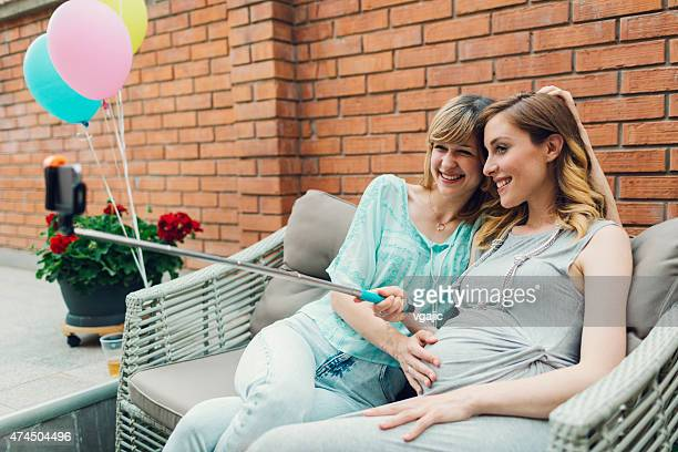 Lesbian Couple Expecting Baby Making Selfie in their backyard.
