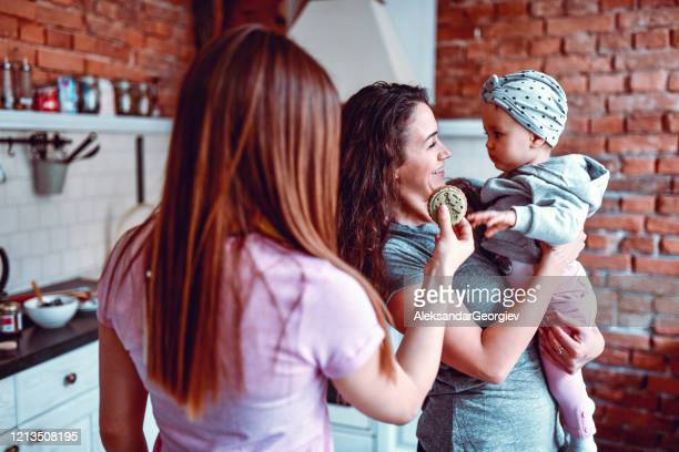 lesbian couple giving cookie to their baby daughter - aunt stock pictures, royalty-free photos & images