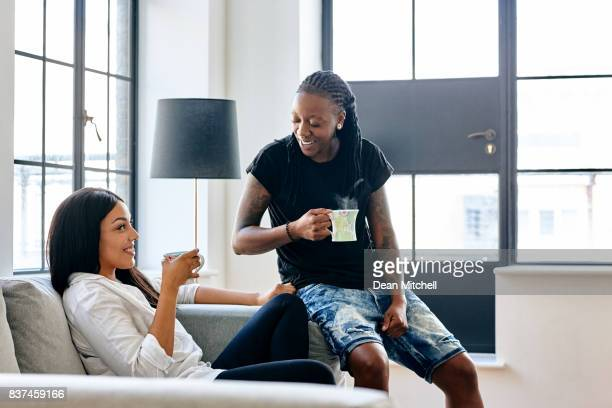 lesbian couple having coffee at home - lesbian date stock pictures, royalty-free photos & images