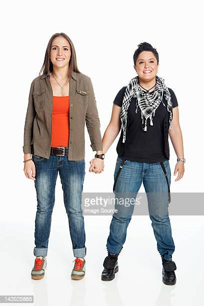 Lesbian couple holding hands against white background