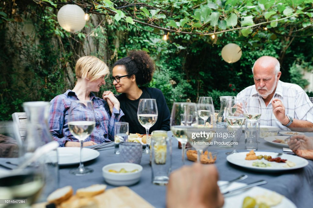 Lesbian Couple Holding Hands At BBQ With Family : Foto de stock