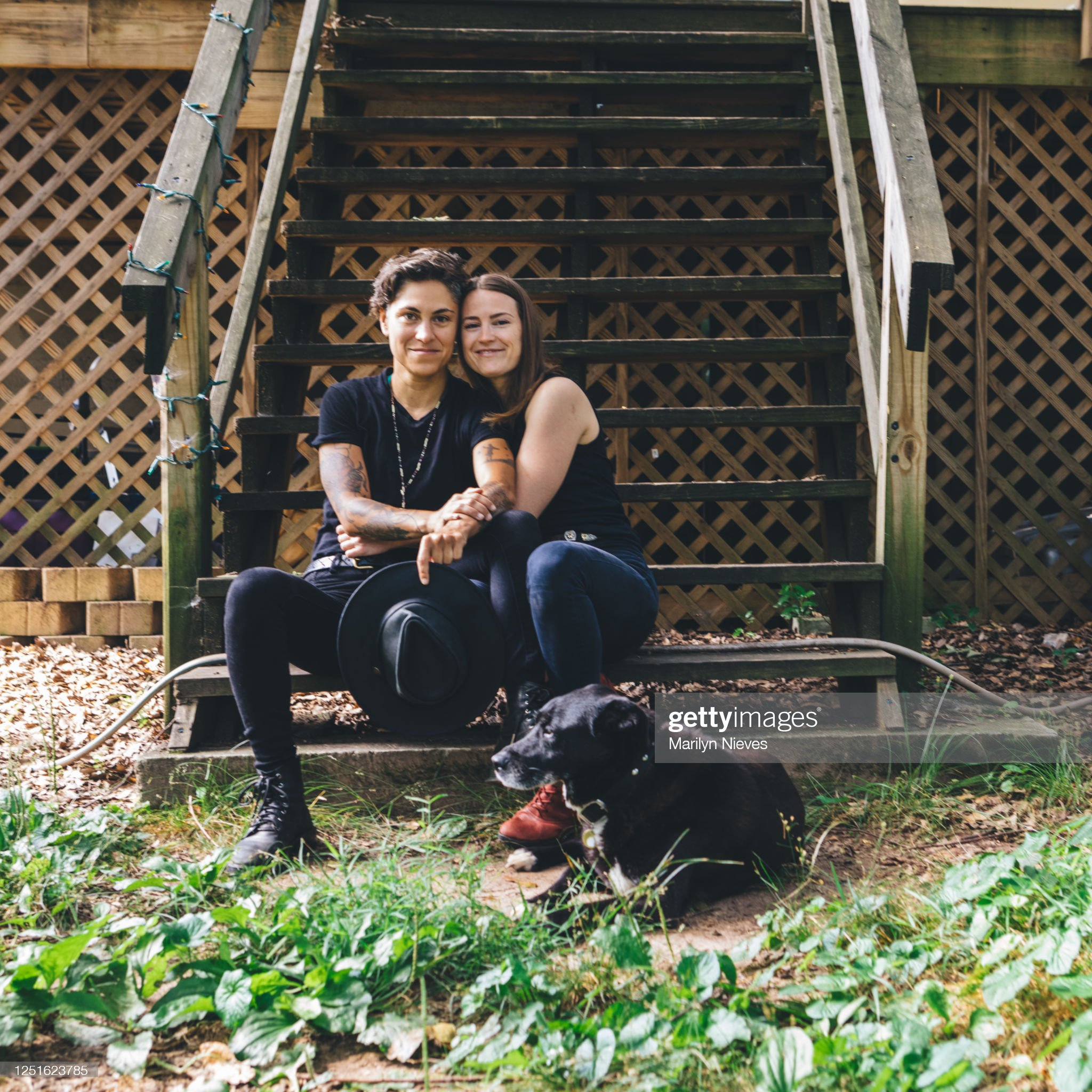 lesbian couple hugging and dog nearby : Stock Photo