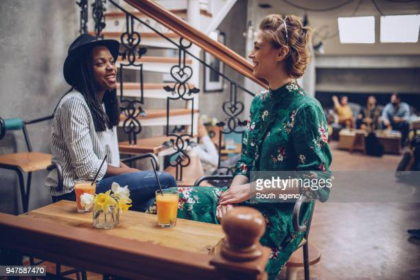 lesbian couple in coffee shop - lesbian dating stock pictures, royalty-free photos & images