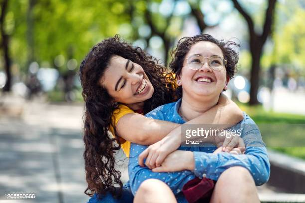 lesbian couple in the park, smiling and hugging - lesbian stock pictures, royalty-free photos & images