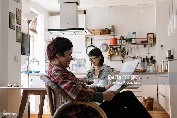 lesbian couple in their kitchen - lgbtq  and female domestic life fotografías e imágenes de stock