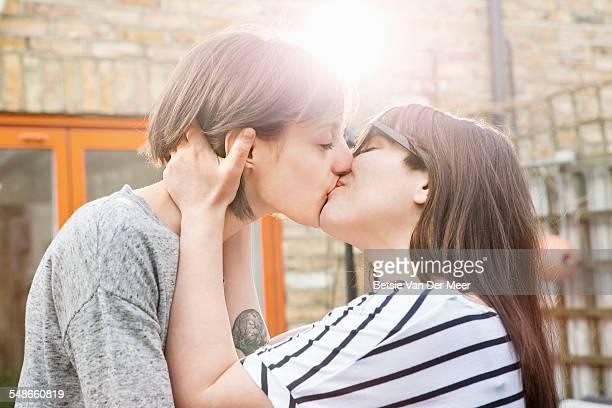 lesbian couple kissing in garden. - lesbica foto e immagini stock